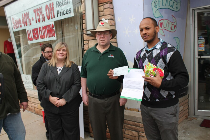 North County Inc. President and CEO Rebecca Zoll, former Ferguson Mayor Brian Fletcher and WIN Wireless owner Nebeyou Teffera stand in front of the I Love Ferguson store. Teffera received a $5,000 grant from the Reinvest North County Fund.