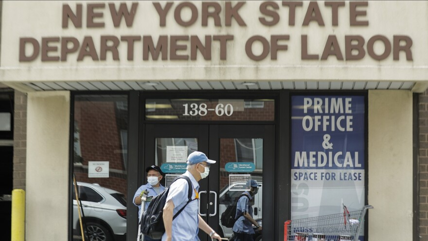 Pedestrians pass a New York State Department of Labor office June 11 in Queens. The Federal Reserve expects the U.S. unemployment rate to still be more than 9% by the end of 2020.