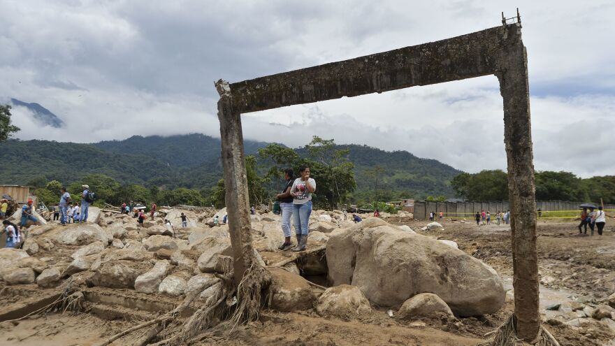 On Sunday, women stare at damage caused Friday night by mudslides following heavy rains in Mocoa, southern Colombia.