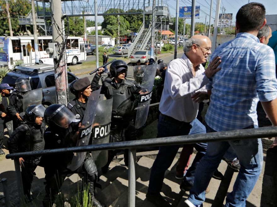 Nicaraguan riot police clear journalists, including Carlos Fernando Chamorro (center), from outside a police station as he tried to speak to the National Police Senior Commissioner Francisco Díaz in Managua, on Dec. 15. Nicaraguan police occupied the headquarters of Chamorro's news organization<em> </em>and of civil and human rights groups.