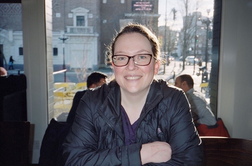 A woman wearing glasses smiling for the camera.