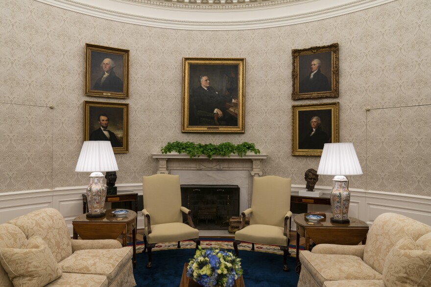 A portrait of Franklin Delano Roosevelt hangs above the Oval Office fireplace. Portraits clockwise from top left: George Washington, Alexander Hamilton, Thomas Jefferson and Abraham Lincoln. King's bust is to the left, a bust of Robert Kennedy is on the right.