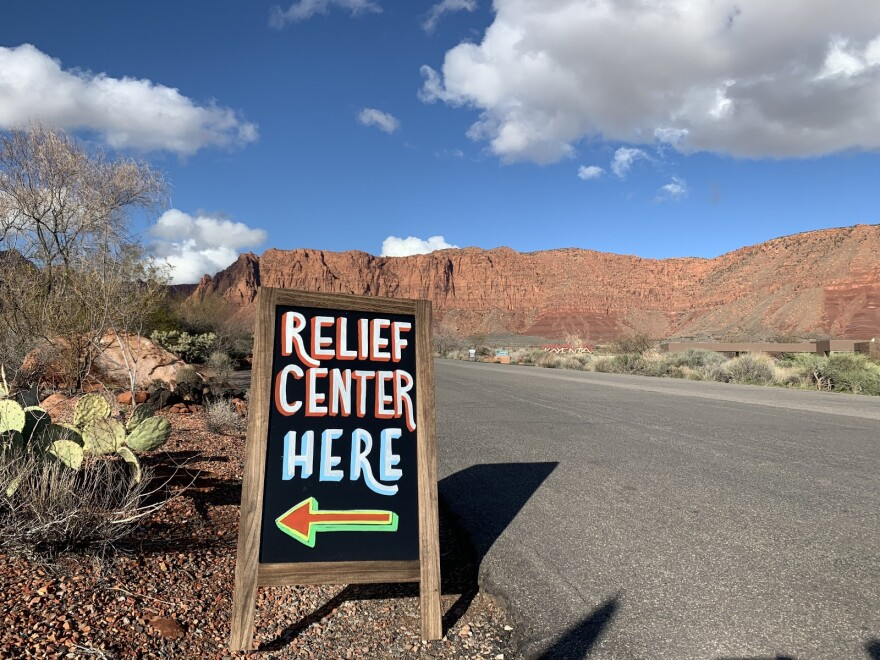"A roadside sign inscribed with an arrow and the words ""relief center here"" stands out against the red cliffs and desert landscape of Ivins, Utah."