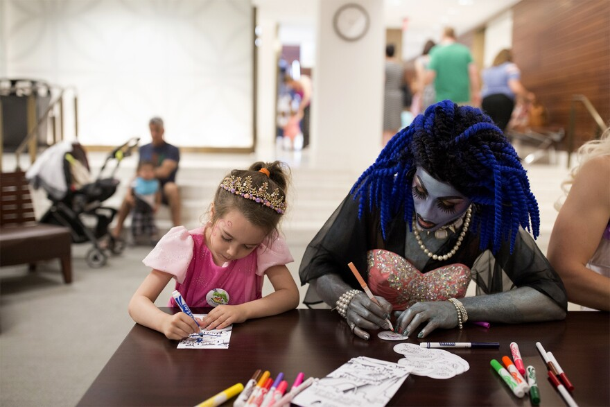 Five-year-old Honore Locker colors alongside Maxi Glamour after Drag Queen Story Hour at St. Louis Public Library's Central Branch.