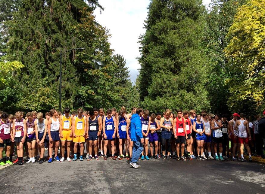 Image of a line of high school boys standing outside, preparing to race.