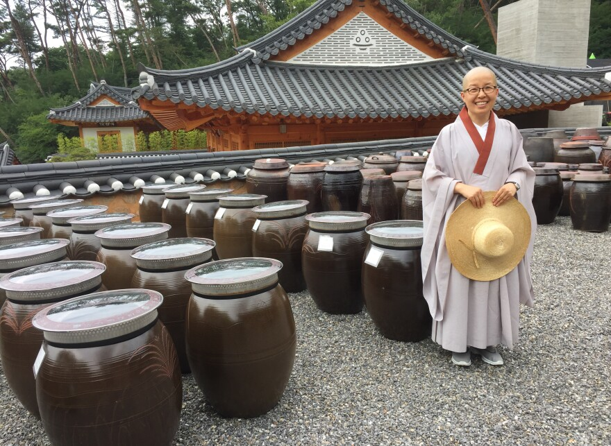 Sun Woo directs the visitor program at Jinkwansa, a Buddhist temple outside Seoul famous for preserving the art of Korean temple food. Behind her are giant jars filled with fermented soybeans.