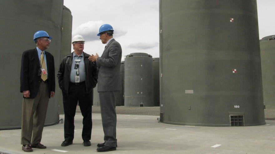 About 70,000 tons of used nuclear fuel sits mostly at power plants across the country. Much is kept underwater in spent fuel pools, but utility companies have been moving the fuel into concrete and steel casks like these in Richland, Wash. Energy Northwest CEO Vic Parrish (center) tours the facility with Reps. Doc Hastings (left) and Jay Inslee.