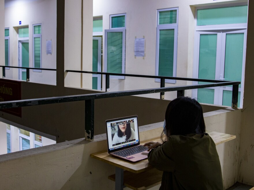 Thu Nguyen attends classes via Zoom at night in the hallway where the WiFi signal is strongest. Like the photographer, Nguyen is a student at a college in the U.S.