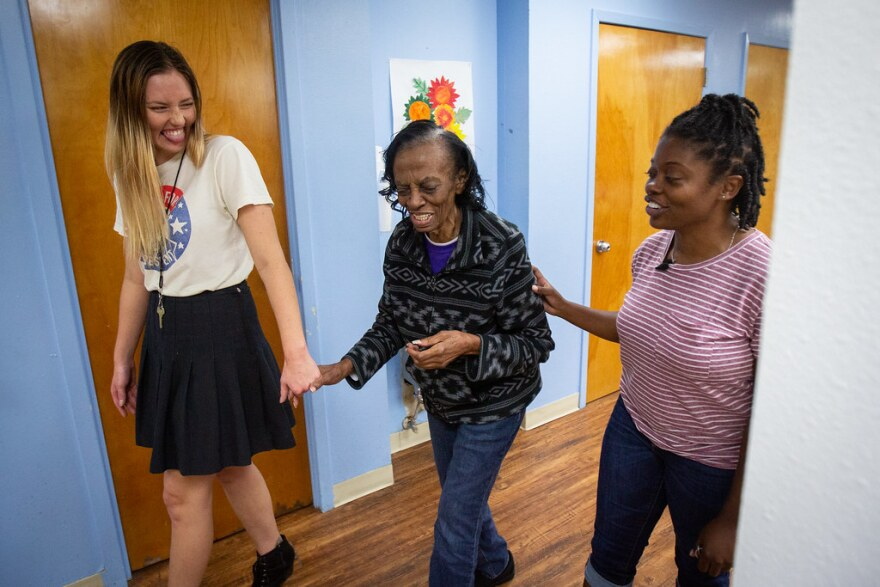 Holly Stoever holds Laura Smith's hand as she walks with Shantiana Smith at the Austin Thrive Social and Wellness Center.