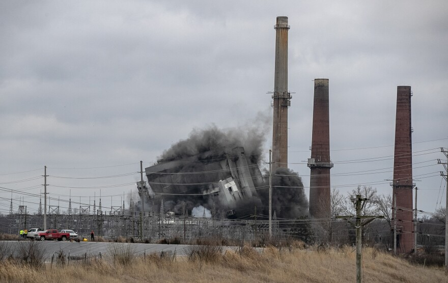 Workers watch from a safe distance as the main structure of the former Wood River Power Plant in East Alton is brought down by explosives Monday.  Three smokestacks that some Madison County residents are concerned could release potentially harmful pollutants were not part of the demolition at the former Dynegy coal fired power plant.