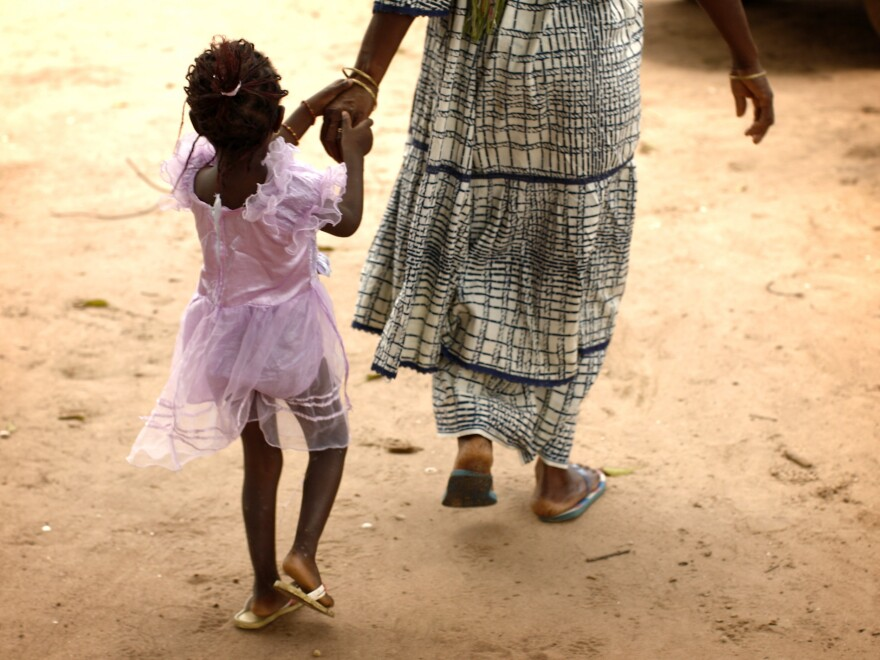 A mother and daughter walk home after attending a community meeting about eradicating female genital mutilation in the western Senegalese village of Diabougo.