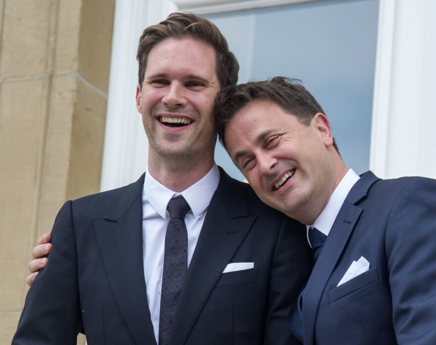 Luxembourg's Prime Minister Xavier Bettel, right, puts his arm around his partner Gauthier Destenay as they leave the town hall after their marriage in Luxembourg on Friday.