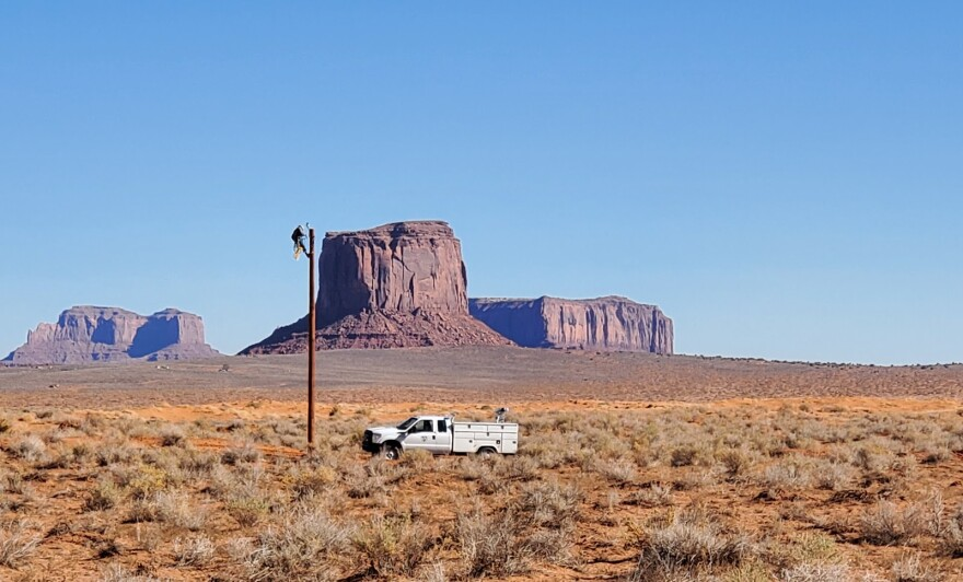 A man climbs to the top of a power pole in front of a red rock butte