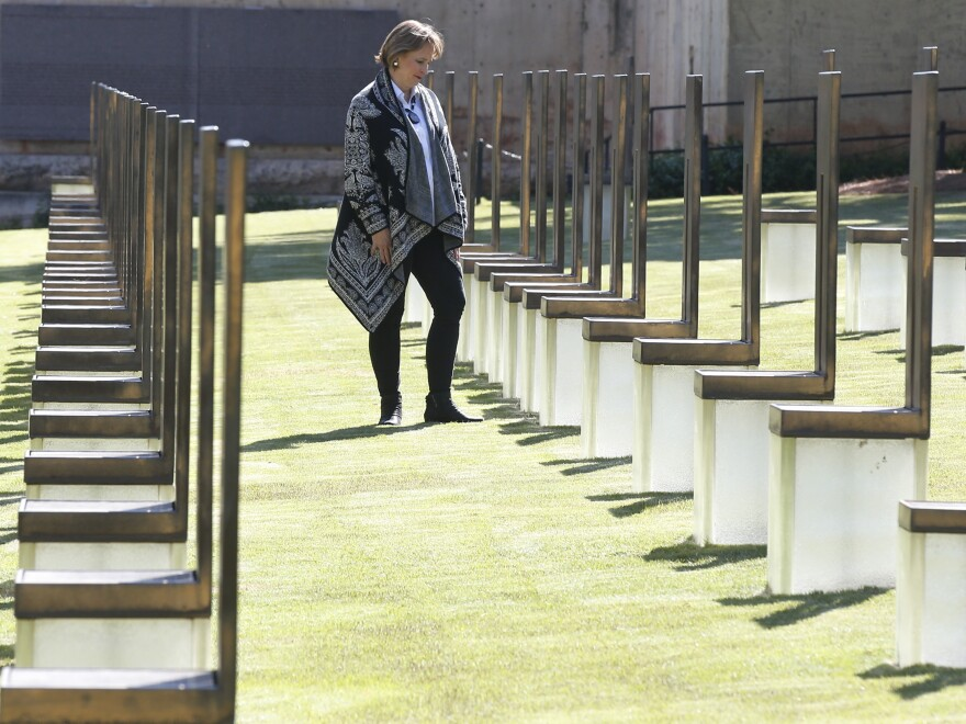 Lynne Gist stands at her sister's chair in the Field of Empty Chairs at the Oklahoma City National Memorial and Museum on Wednesday. Gist lost her sister, Karen Gist Carr, when a truck bomb ripped through a federal building in downtown Oklahoma City and killed 168 people 25 years ago.