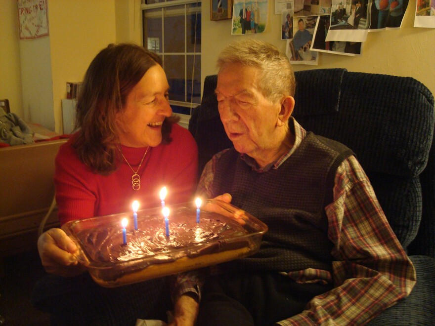 Susan Cerulean holding a cake with lit candles sitting next to older man