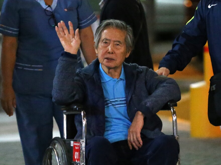 "Peru's former President Alberto Fujimori waves to supporters as he is wheeled out of a clinic in January after receiving a ""medical pardon."""