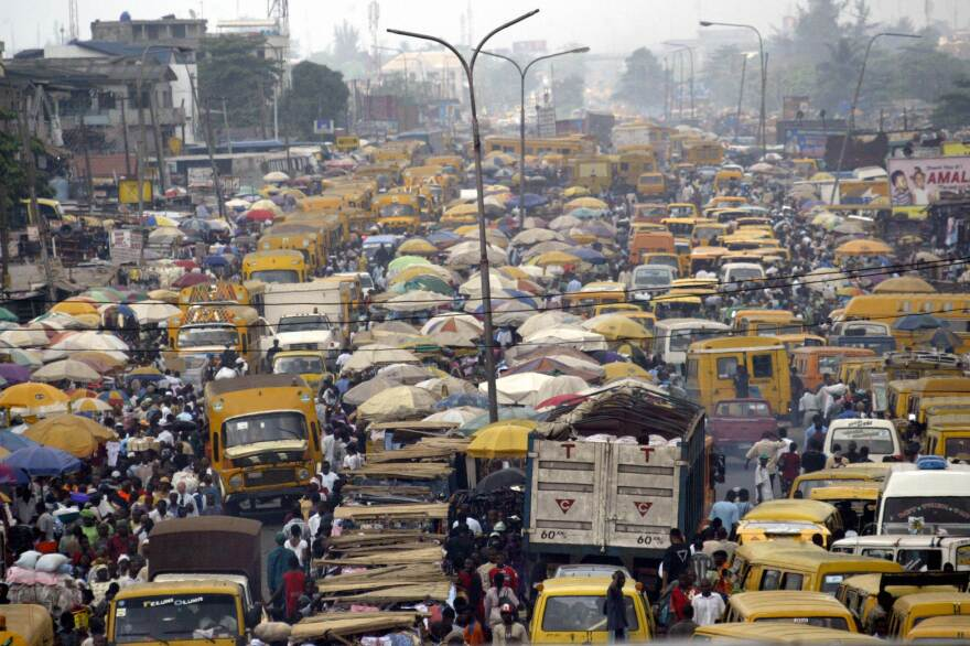 People walk struggling for space between public transport buses and trucks at the burstling Oshodi bus stop in Lagos 06 February 2006. Lagos is reputed as one of the mostly densely populated city in the world with population more than 14 million. AFP PHOTO/PIUS UTOMI EKPEI (Photo credit should read PIUS UTOMI EKPEI/AFP/Getty Images)