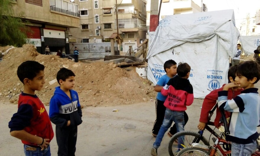 Syrian children wait as a checkpoint that once separated their Damascus suburb from government-held areas is bulldozed. Rebels left the town in a truce negotiated with the help of local activists and notables.