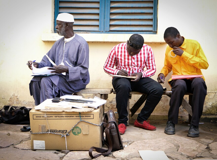Getting postcards from Timbuktu, Mali, to destinations around the world is a lengthy process. Daba Traoré, center, takes the postcards — which have been flown in from Timbuktu on a U.N. plane — to the central post office in Bamako.