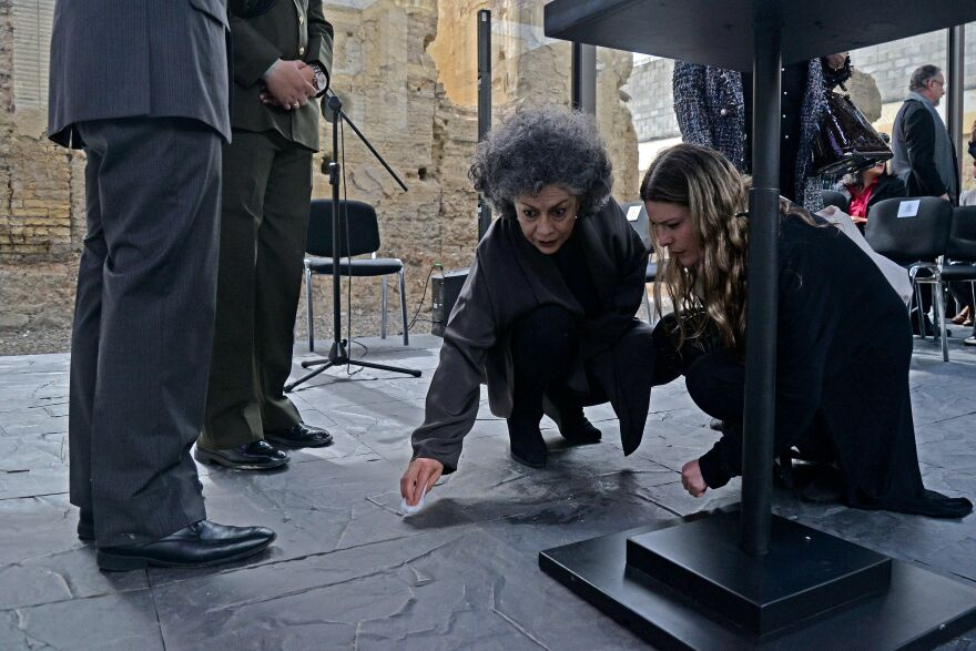 Colombian sculptor Doris Salcedo (center) cleans a spill on the floor during the pre-inauguration of her peace monument titled <em>Fragmentos</em> (Fragments), for which she used metal melted-down from the weapons handed over by FARC guerrilla fighters to make the floor, in Bogotá on July 31.