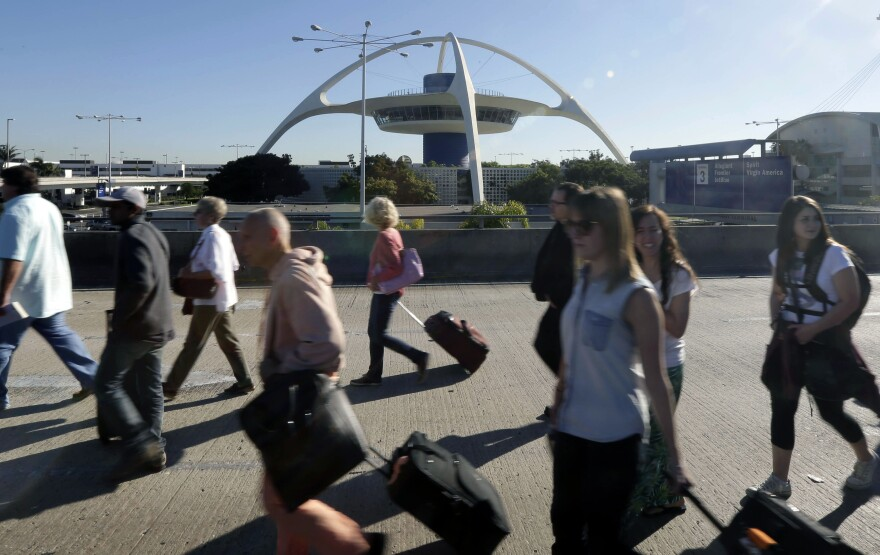 People exit Los Angeles International Airport in Los Angeles on Friday.
