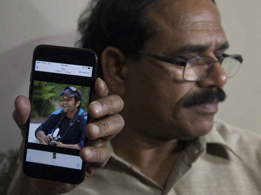 A man shows a cellphone picture of Alok Madasani, an engineer who was injured in Wednesday's shooting, in front of Madasani's father, Jaganmohan Reddy, in the Indian city of Hyderabad.