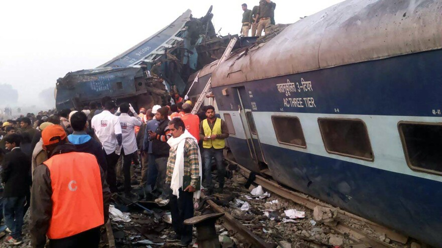 Indian rescue workers search for survivors in the wreckage of a train that derailed near Pukhrayan in Kanpur district on Sunday.