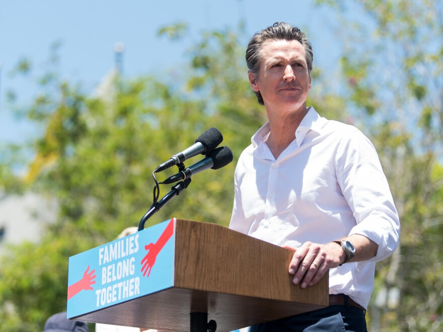 """California Lt. Gov. Gavin Newsom speaks at a """"Families Belong Together"""" march in Los Angeles on June 30. Newsom is leading the polls in his campaign for governor."""