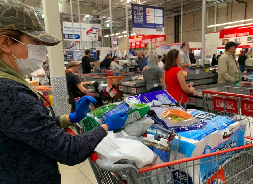 Customers wait in line to buy water and other supplies, on fears that the coronavirus, COVID-19, will spread and force people to stay indoors, at a Costco in Burbank, California.