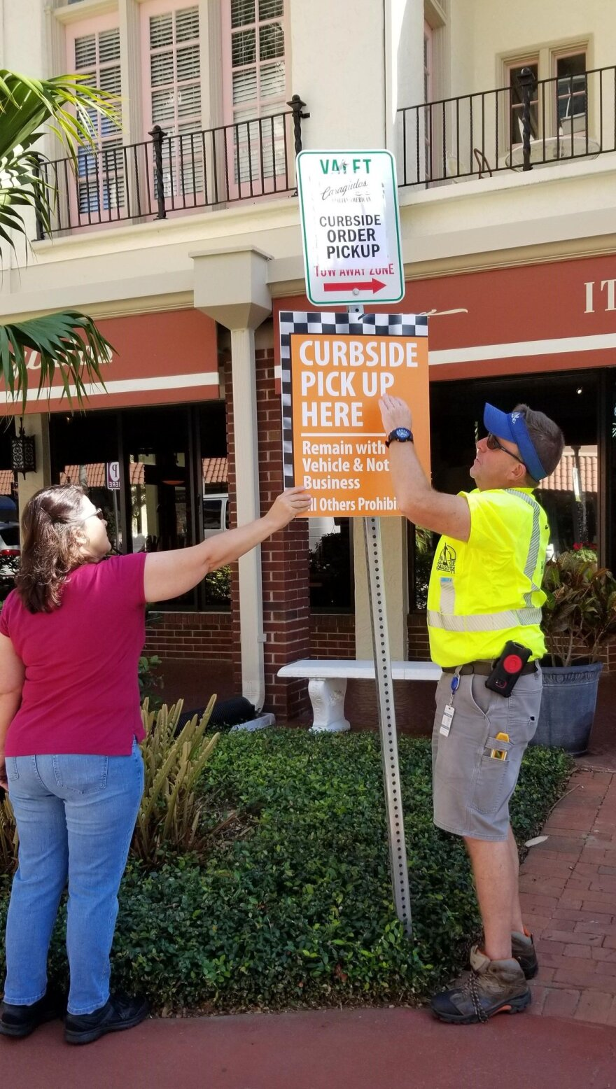 Workers putting up a restaurant curbside parking sign.