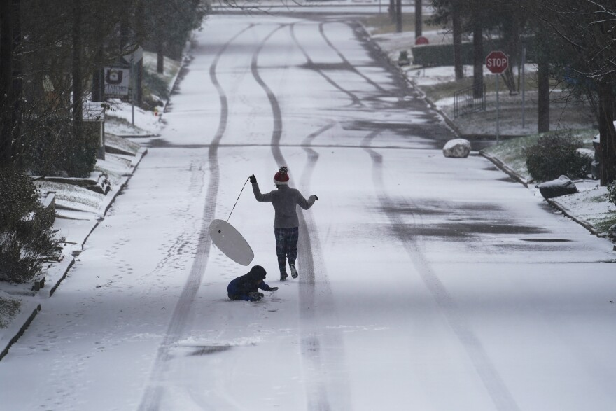 Child running down snowy road with boogie board and dog.