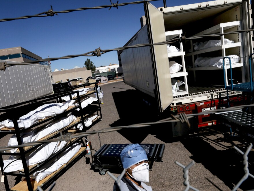 An inmate from the El Paso County detention facility prepares to load bodies wrapped in plastic into a refrigerated temporary morgue trailer.