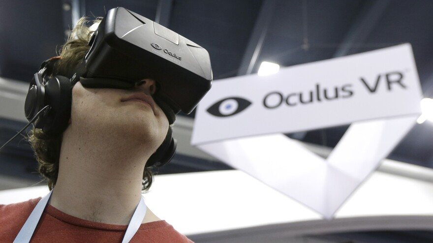 Peter Mason tries the Oculus virtual reality headset at the Game Developers Conference in San Francisco earlier this year. Some see Facebook's acquisition of the company as a turning point.