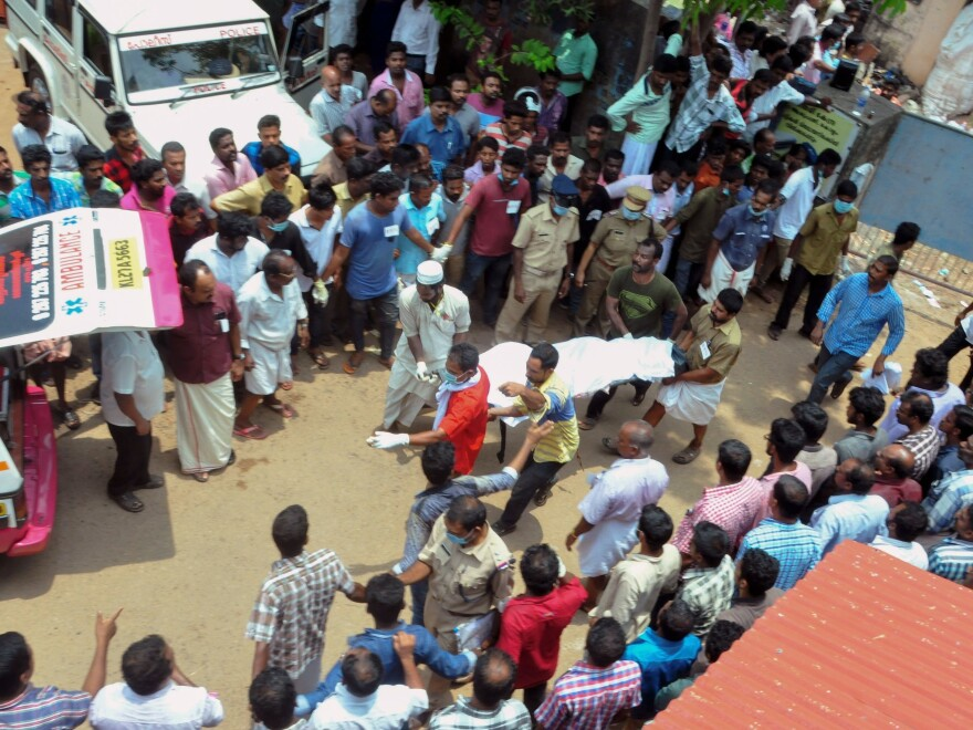 Men carry a body to an ambulance after the fire at a temple in Kerala on Sunday.