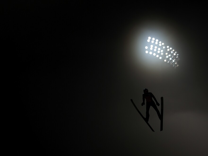 A competitor jumps through the fog during the Ski Jumping Men's Large Hill official training on day 9 of the 2014 Winter Olympics in Sochi.