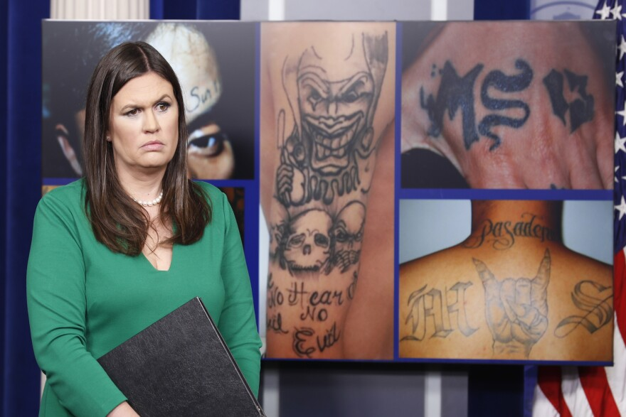 White House press secretary Sarah Huckabee Sanders stands in front of pictures of MS-13 gang tattoos during a press briefing at the White House in Washington, Thursday, July 27, 2017. (Alex Brandon/AP)