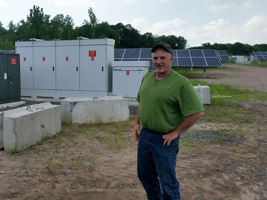 Kevin Sullivan in front of the solar array on his property.