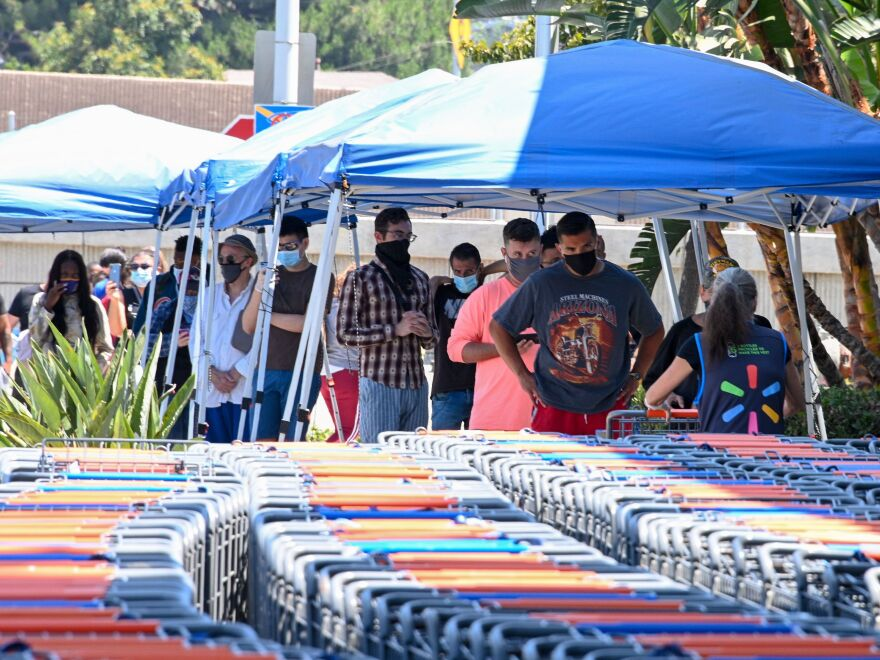 People wearing face coverings wait to shop at Walmart on Wednesday in Burbank, Calif. The state has seen more than 425,000 cases, including more than 12,000 new cases on Wednesday.