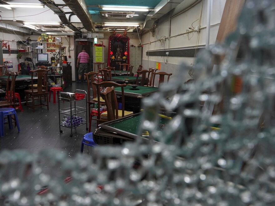 Broken glass scattered around a mahjong shop operated by mainland Chinese damaged by demonstrators during a protest in Hong Kong, on Sunday.