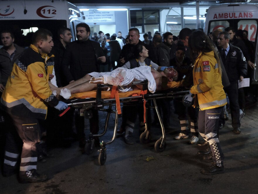 Rescue workers and medics carry a wounded person after attacks in Istanbul late Saturday. Two explosions struck outside a major soccer stadium in Istanbul after fans had gone home.