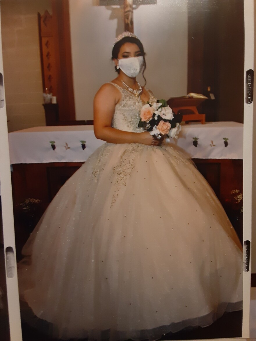 A girl poses for the camera wearing a blush pink ballgown and a matching face mask. She is holding flowers.