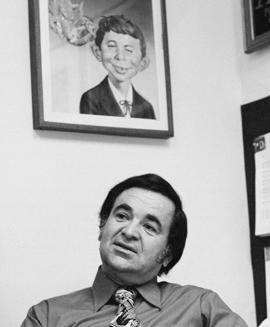 Editor Al Feldstein works on page layouts in his office at <em>Mad</em> magazine's New York headquarters in 1972. A poster with the iconic character Alfred E. Neuman hangs on the wall behind him.