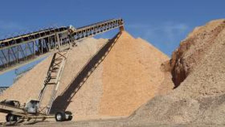 A mobile conveyer spews finished wood chips into giant mounds at Highland Pellets.