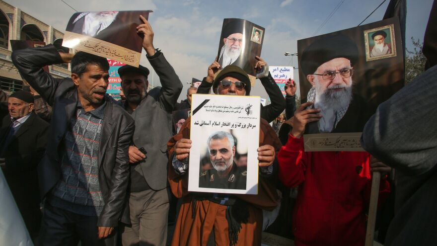 Iranian demonstrators hold posters of slain Maj. Gen. Qassem Soleimani (center) and the country's supreme leader, Ayatollah Ali Khamenei, during a rally Friday in the capital, Tehran. The U.S. strike on the military leader in Baghdad has elicited warnings of retaliation from Iran.