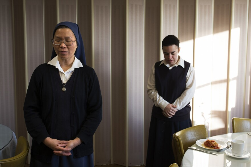 Sister An Mei and postulant Cecilia Cicone pray before eating breakfast in the convent of the Daughters of St. Paul in Crestwood.