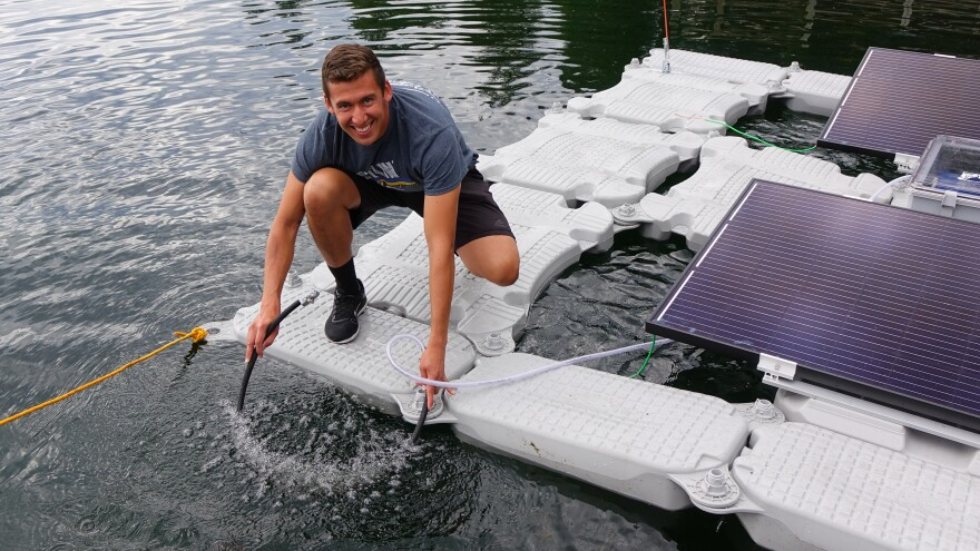 Oregon Institute of Technology student Juan Villarreal holds the aeration hose that will add dissolved oxygen to Upper Klamath Lake.