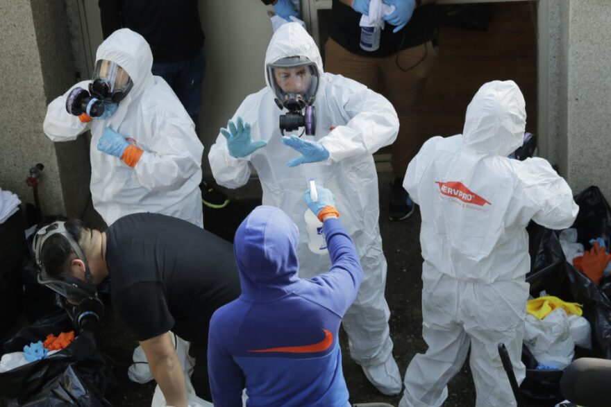 Servpro cleaning workers are sprayed as they exit the Life Care Center in Kirkland, Wash., Thursday, March 12, 2020, at the end of a day spent cleaning inside the facility near Seattle. (Ted S. Warren/AP Photo)