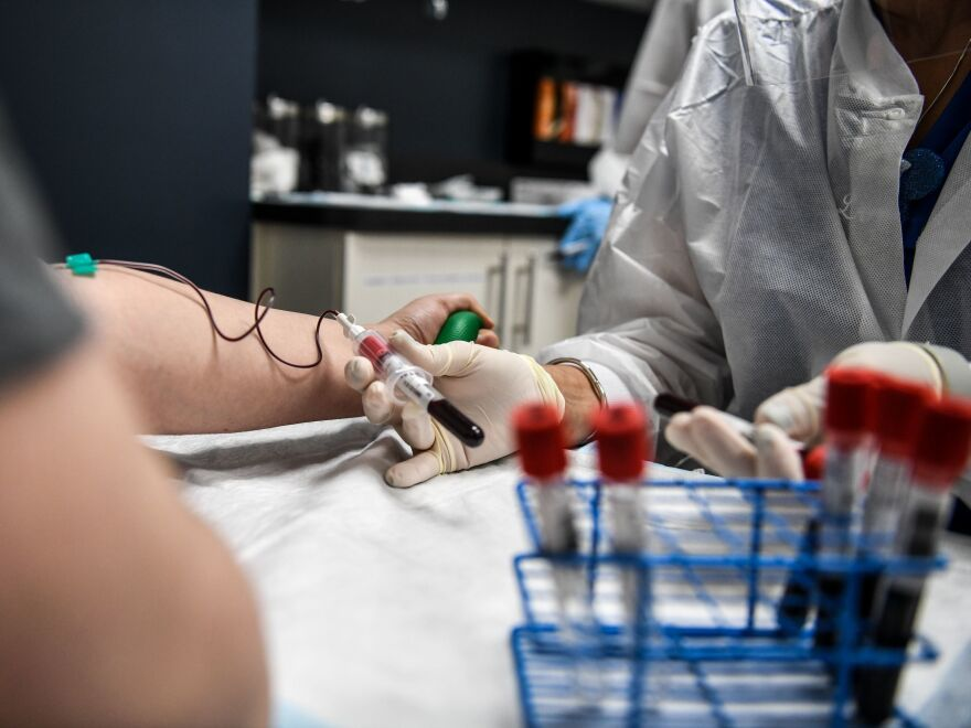 A researcher takes blood samples from a patient as she participates in a COVID-19 vaccine study last month at the Research Centers of America in Hollywood, Fla.