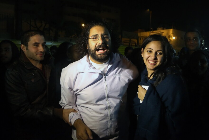 Alaa Abdel Fattah (center), a prominent activist and a leading figure in the 2011 uprising against Egyptian autocrat Hosni Mubarak, is welcomed by his wife after he was released from the main central security office in Cairo on Sunday.