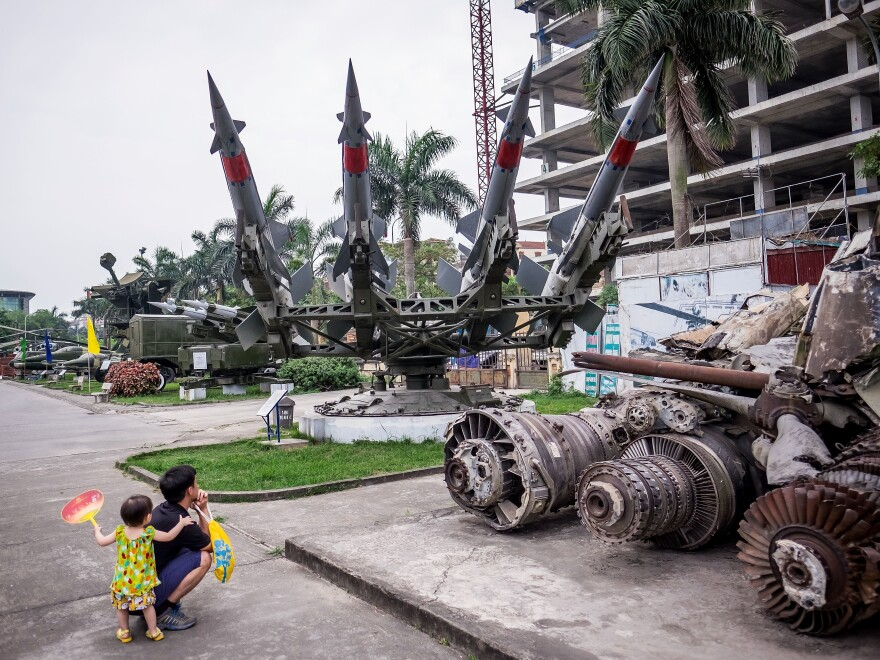 A Vietnamese man and child look at models of weapons at the Vietnam People's Air Force Museum on May 23 in Hanoi. President Obama announced during the first day of his visit this week that the U.S. is fully lifting its embargo on sales of lethal weapons to Vietnam.